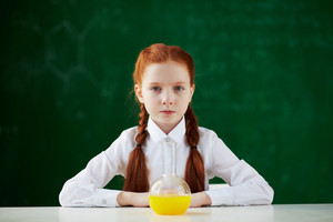 Portrait Of Schoolgirl Sitting At Workplace With Chemical Liquid In Front
