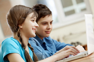 Portrait Of Teenage Girl Typing With Her Classmate At Background