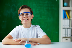 Portrait Of Smiling Schoolboy Sitting At Workplace With Chemical Liquid In Front