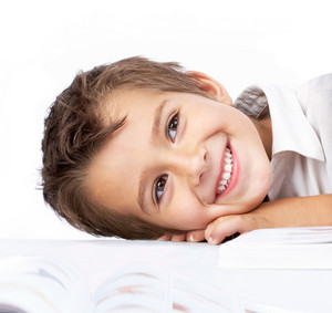Portrait Of A Little Schoolboy Lying On Table And Smiling