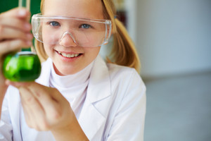 Portrait Of Cute Schoolgirl Holding Tube With Chemical Liquid And Looking At Camera