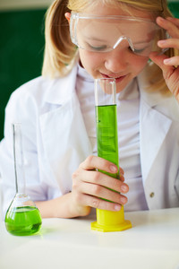 Portrait Of Cute Schoolgirl Smelling Chemical Liquid In Tube