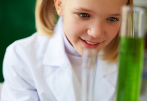 Portrait Of Cute Schoolgirl Studying Chemical Liquid In Laboratory