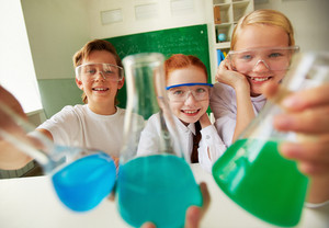 Three Happy Schoolchildren Holding Tubes With Chemical Liquids
