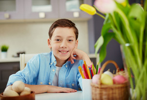 Portrait Of A Boy Sitting At Table At Easter Day