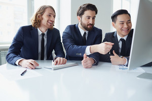 Three Businessman Discussing Project In Meeting Room