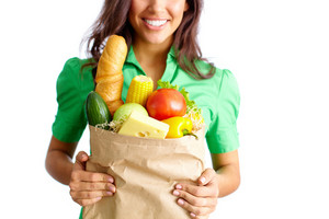 Image Of Paper Packet Full Of Different Kinds Of Food Held By Female