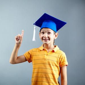 Portrait Of Happy Boy Pointing Upwards On Grey Background