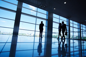 Silhouettes Of Office Worker Standing By The Window And Two Business Partners Communicating While Walking Near By