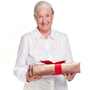 Portrait Of Elderly Female With Giftbox Looking At Camera