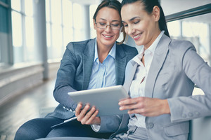 Image Of Two Happy Businesswomen Discussing Computer Project