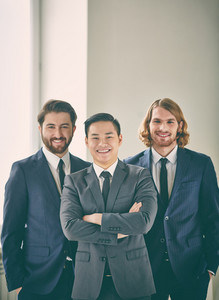 Vertical Portrait Of Successful Business Partners Smiling And Looking At Camera