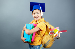 Portrait Of Happy Schoolkid With Backpack And Books