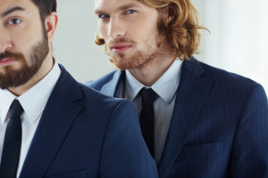Young Businessman Looking At Camera With His Colleague Near By