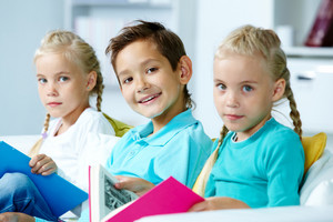 Smart Schoolboy Looking At Camera Between Twin Girls