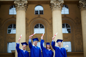 Group Of Cheerful Students In Graduation Gowns Showing Their Certificates