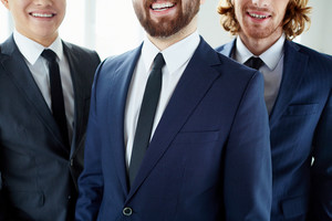 Close-up Of Toothy Smiles Of Businessmen In Elegant Suits