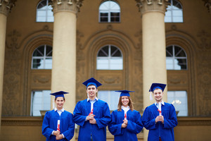 Group Of Smart Students In Graduation Gowns Holding Certificates