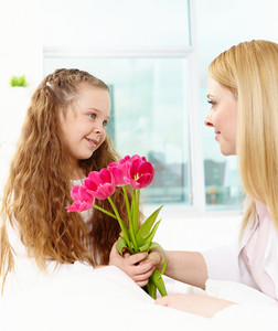 Adorable Girl Giving Bunch Of Tulips To Her Mother