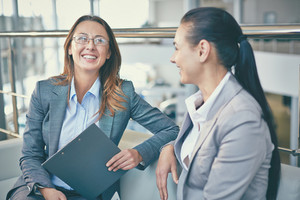 Image Of Smiling Businesswoman With Clipboard Telling Something To Her Colleague