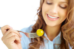 Close-up Of Frsh Cherry Tomato On Fork Held By Pretty Girl