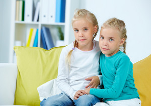 Portrait Of Twin Girls Sitting On Sofa
