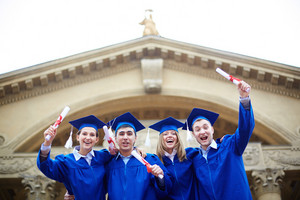 Group Of Ecstatic Students In Graduation Gowns Holding Diplomas