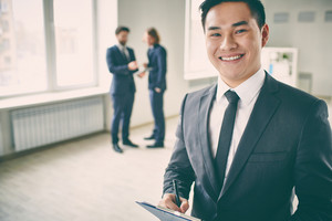 Close-up Portrait Of A Young Successful Manager With Clipboard Posing At Camera While His Colleagues Talking On The Background
