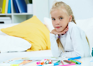 Portrait Of Lovely Girl With Her Pictures And Colorful Pencils Near By