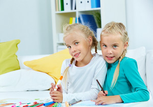 Portrait Of Lovely Twins With Colorful Pencils Looking At Camera