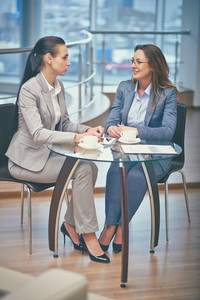 Image Of Two Friendly Businesswomen Talking By The Cup Of Coffee In Office