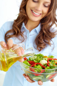 Close-up Of Smiling Female Pouring Olive Oil Into Vegetable Salad