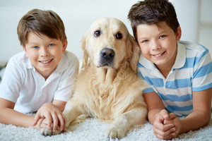 Portrait Of Happy Siblings With Their Pet Having Rest At Home