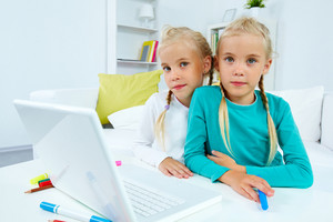 Portrait Of Lovely Twins Looking At Camera With Laptop In Front