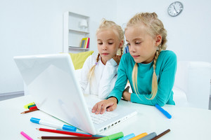 Portrait Of Twin Girls Studying In Front Of Laptop