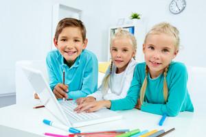 Smart Schoolchildren Working With Laptop At Home