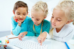 Smart Schoolboy Looking At Twin Girls Touching Laptop Keys
