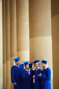 Group Of Smart Students In Graduation Gowns Having Chat