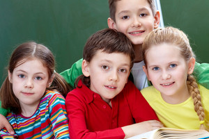 Team Of Four Classmates Looking At Camera In Classroom
