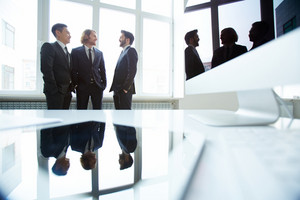 Three Businessman Discussing Ideas In Meeting Room