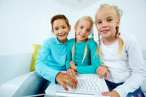 Smart Schoolchildren With Laptop Looking At Camera
