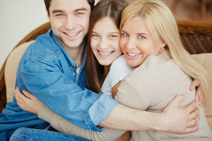Portrait Of Happy Family Of Three Embracing And Looking At Camera