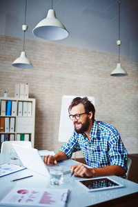 Young Businessman In Casualwear Using Laptop In Office