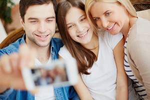 Young Man Holding Cellular Phone With Happy Daughter And Wife Near By