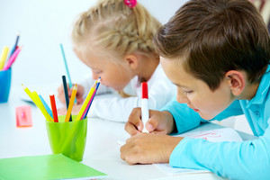 Portrait Of Cute Boy Drawing With Colorful Pencils And His Classmate On Background