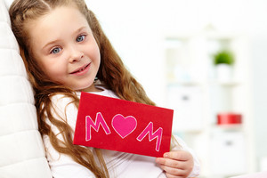 Portrait Of Happy Girl Showing Envelope With Congratulation Card And Looking At Camera