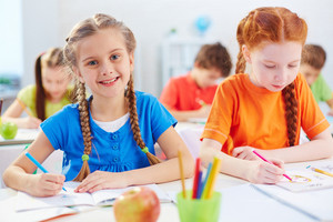 Pretty Pupil Drawing At Lesson With Her Friend Near By