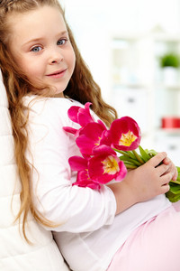 Portrait Of Happy Girl With Tulip Bouquet Looking At Camera