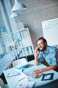 Happy Young Businessman Speaking On Cellphone While Working In Office