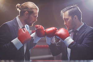 Two Competitive Businessmen In Suits And Boxing Gloves Attacking One Another